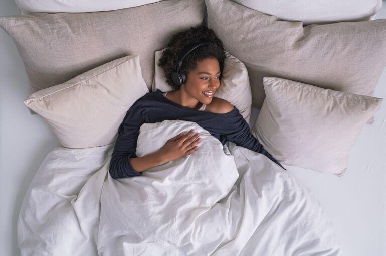 Une femme rayonnante dans son lit en écoutant de la musique.