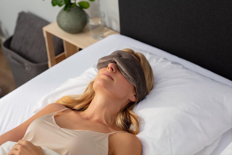 Een vrouw ligt op haar rug met haar hoofd op een Original kussen. Ze draagt een slaapmasker.