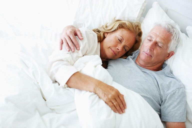 Un homme et une femme sont allongés ensemble sur le lit. La femme est allongée la tête sur la poitrine de son mari.