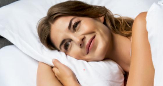 Une femme est allongée sur le côté, la tête sur un oreiller. Elle lève les yeux et rayonne.